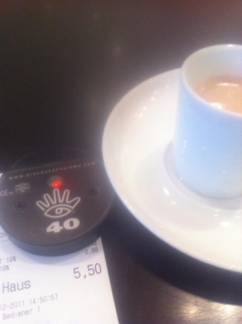 Tasse mit einem schwarzen, runden Kunststoffgerät mit roter Leuchtdiode.